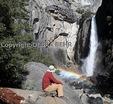 Hiker sits by Lower Yosemite Fall