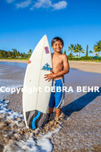 Young Kauai surfer with surfboard at Hanalei Bay