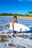 Young surfer on Kauai with surfboard