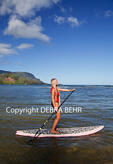 Stand up paddleboarder explores Hanalei Bay; Mt. Makana, called Bali Hai, is in the background