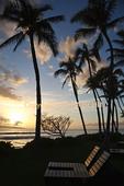 Golden light at sunset illuminates chairs off walkway at Kaanapali Beach on Maui