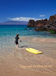 Young girl with boogie board and snorkelers at Black Rock at Kaanapali Beach