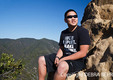 Hiker rests on rocky overlook by Skull Rock off the Temescal Ridge Trail