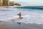 Boy with skim board awed by large waves generated by south swell at Kaanapali Beach on Maui