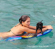 Young woman with puppy in ocean off the Big Island of Hawaii