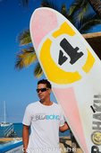 Ocean Sports team member with surfboard at Anaehoomalu Bay on the Big Island of Hawaii