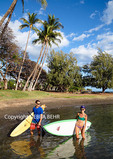Couple with surfboard and stand up paddleboard on West Maui beach
