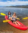 Women in two-person kayak at shoreline of Lake Tahoe