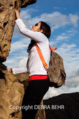 Woman explores rock formation above the Temescal Ridge Trail in the Santa Monica Mountains