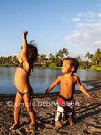 Children play at Anaehoomalu Beach, with the historic fish pond in the background