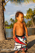 Boy at Anaehoomalu Beach, with the historic fishpond in the background