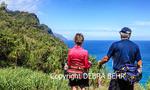 Hikers on the Kalalau Trail gaze at the Na Pali Coastline on Kauai
