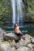 Woman relaxes by Hanakapiai Falls, reached on a four-mile, one-way trail