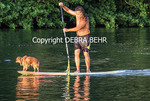 Keoni Durant and his dog, Milo, on surfboard in the Hanalei River