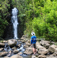 Hiker by waterfall reached by hike from the Hana Highway