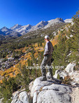 Hiker at overlook off the Mono Pass Trail looks at Little Lakes Valley in Rock Creek Canyon