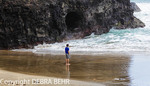Hiker looks at rough surf by sea cave at Hanakapiai Beach reached by the Kalalau Trail