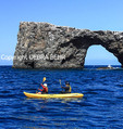 Kayakers paddle by Arch Rock off Anacapa Island in Channel Islands National Park