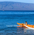 Boy paddles outrigger canoe during practice off Canoe Beach on Maui