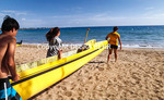 Paddlers carry outrigger canoe to sea at Canoe Beach on Maui