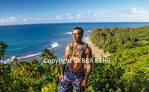 Hiker on the Kalalau Trail, with Kee Beach in distance