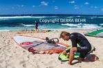 Windsurfer adjusts equipment at Hookipa Beach Park
