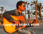 Golden light on guitarist playing at coastal walkway at Santa Monica beach