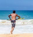 Skimboarder runs into sea at Makena Beach on Maui