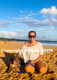 Young woman and her dog, which she rescued on Maui, at Makena Beach, with rainbow in distance