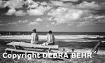 Men watch windsurfers at Hookipa Beach