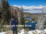 Tourist looks down at Twin Lakes from overlook at Mammoth Lakes Basin in Mammoth Lakes