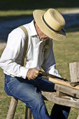 Man demonstrating the use of a drawknife at Millbrook Village