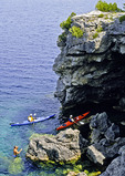 Kayakers and Swimmer Exploring a Lake Cave on the Georgian Bay