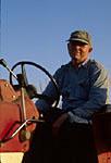 Farmer on tractor harvesting grain