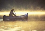 Man paddling canoe on misty morning