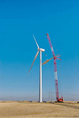 Wind turbine construction: crane lifting last blade into position for attachment to hub