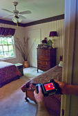 Thermal imaging:  technician using infrared camera to identify air leakage points during home energy audit.  (home dpressurized with blower door).