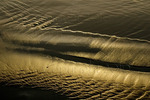 Abstract design in beach sand reflecting sunset lighting