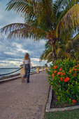 Attractive woman walking at dusk in public waterfront park, Frederiksted, St Croix, US Virgin Islands