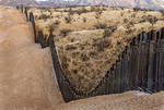 US Border Fence, east of Nogales Arizona USA, constructed autumn and winter of 2008, viewed from US side, looking southeast, note fence following steep hilly terrain.