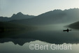 Jane Gildart (photographer's wife) paddles across early morning reflection on  Kintla Lake; Glacier National Park, Montana. USA