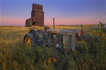 Old tractors and grain elevtaor in ghost town