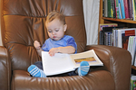 Baby boy sitting on chair looking at book