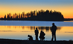 Family on shore of Astotin Lake at sunset