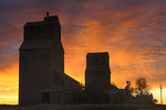 Old grain elevators in ghost town at sunrise