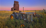 Grain elevator and old tractors in ghost town