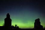 Old grain elevators in ghost town with stars and northern lights (aurora borealis)