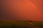 Rainbow and setting sun during prairie storm. West Block