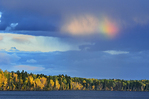 Partial rainbow and storm light on Waskasiu Lake