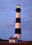 Light shining from Bodie Island Lighthouse at dusk.